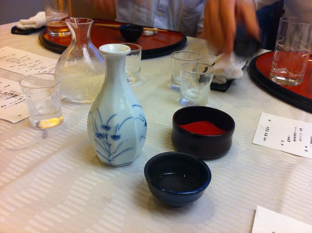Japoński tradycyjny posiłek wstylu kaiseki: nihonshu (sake) naciepło