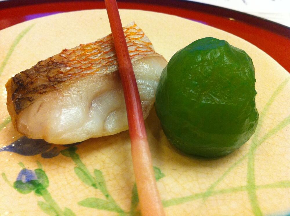 Japoński tradycyjny posiłek wstylu kaiseki: grillowana ryba ryba, śliwka nasłodko imłody pęd imbiru
