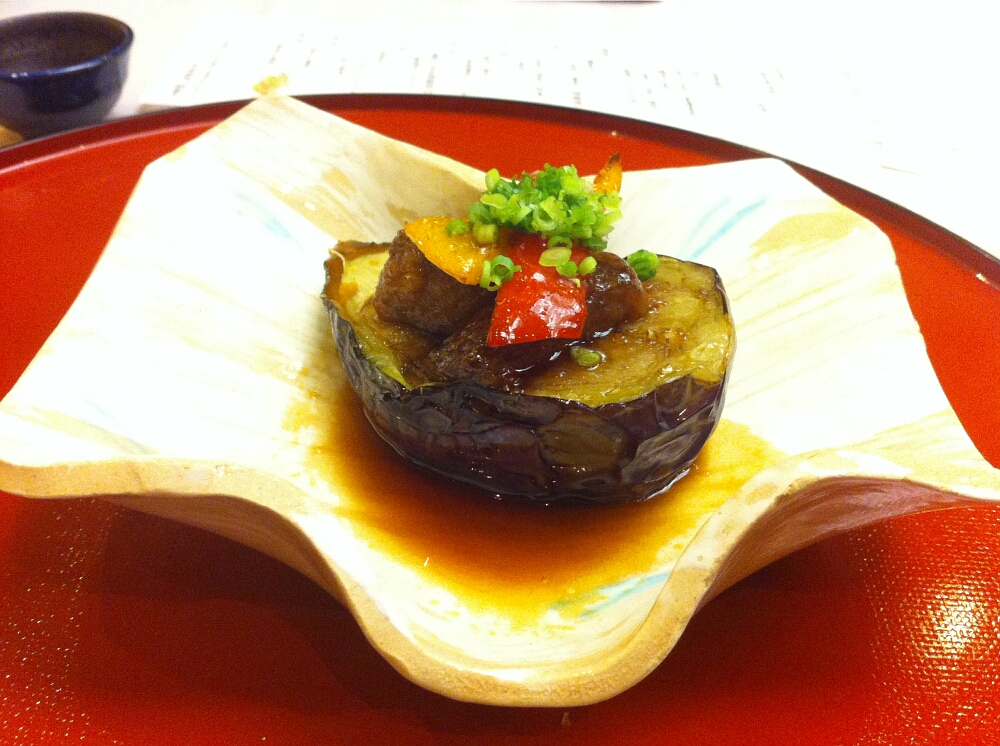 Japoński tradycyjny posiłek wstylu kaiseki: bakłażan zwatróbką, papryką iszczypiorkiem
