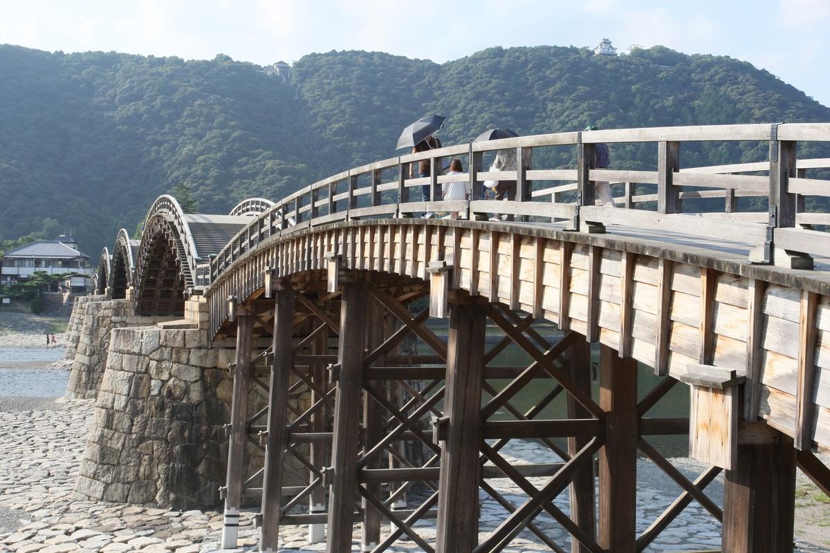 Ciekawe miejsca wJaponii: zamek Iwakuni-jō (nahoryzoncie polewej) górujący nadrzeką Nishiki, Iwakuni, Japonia